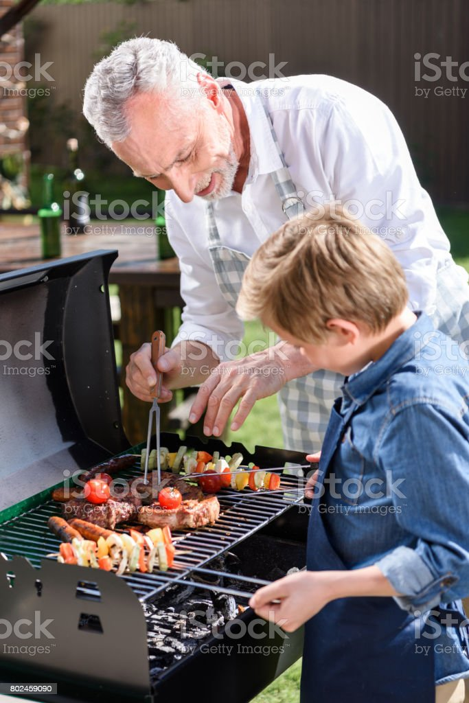grey haired grandfather with his grandson preparing meat and vegetables on grill outdoors stock photo