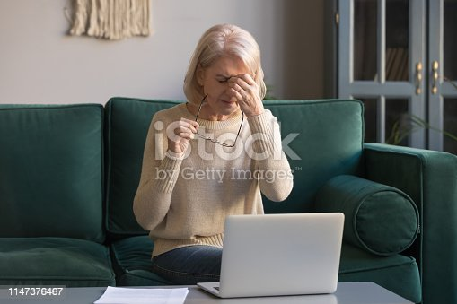 1049512672 istock photo Grey haired mature woman massaging nose bridge, eyestrain concept 1147376467