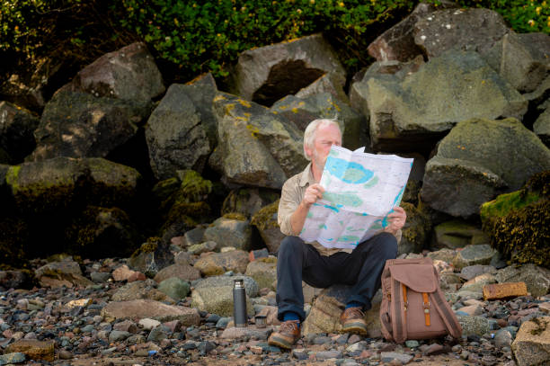Grey haired senior man sitting on rocks at the shore looking at a map he is holding An active over 60s man on his own sitting on a rock at the coast. The section of coast is in Dumfries and Galloway, south west Scotland. The man has came equipped for a day out with a backpack and a flask. johnfscott stock pictures, royalty-free photos & images