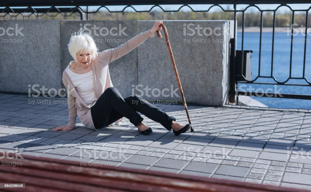 Grey headed woman feeling helplessness in the street stock photo