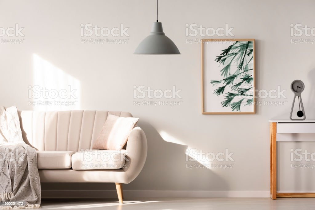 Grey lamp in bright living room interior with poster next to beige sofa. Real photo stock photo