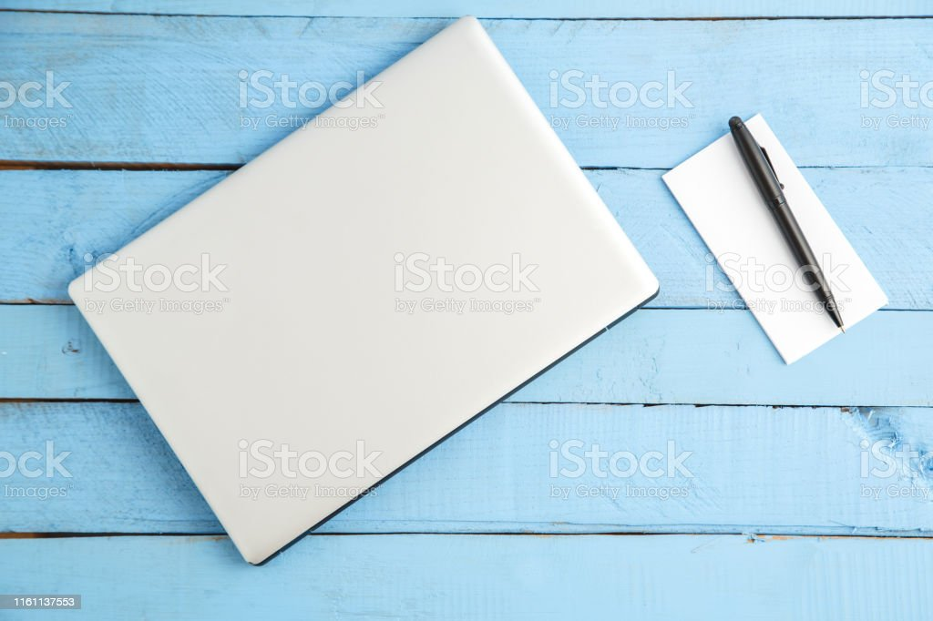 grey laptop and paper notebook with black pen on blue wooden...
