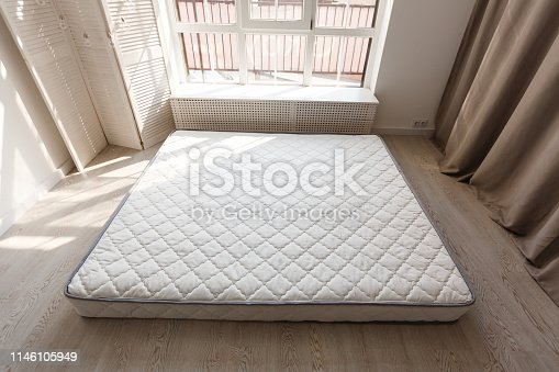 508860888 istock photo Grey mattress on the floor against designer screen in spacious bedroom with grey chair against dark curtain 1146105949
