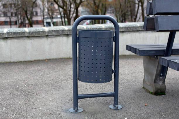 Grey metal trash waste bin in the park stock photo