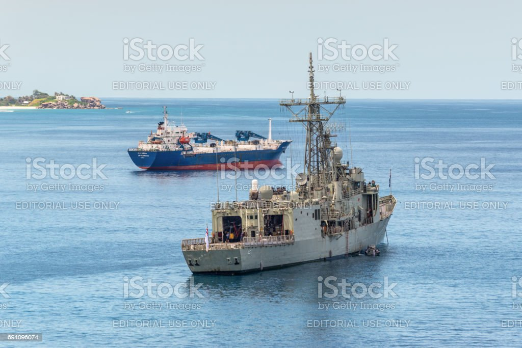 Grey modern frigate of the Royal Australian Navy anchored in the bay of Victoria, Mahe island, Seychelles stock photo