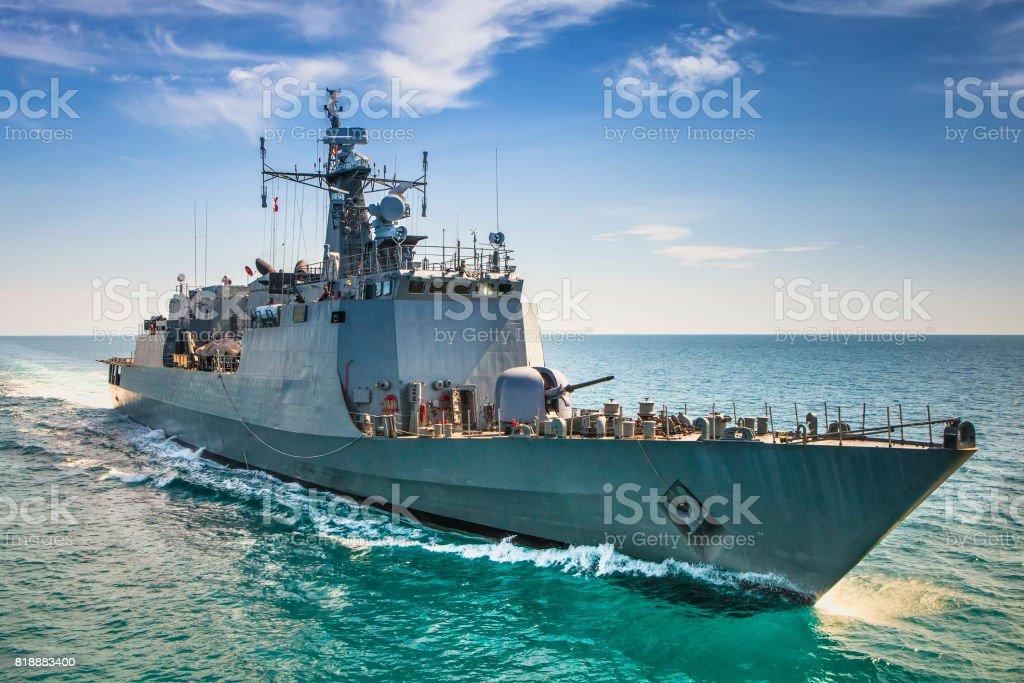 Grey modern warship sailing in the sea stock photo