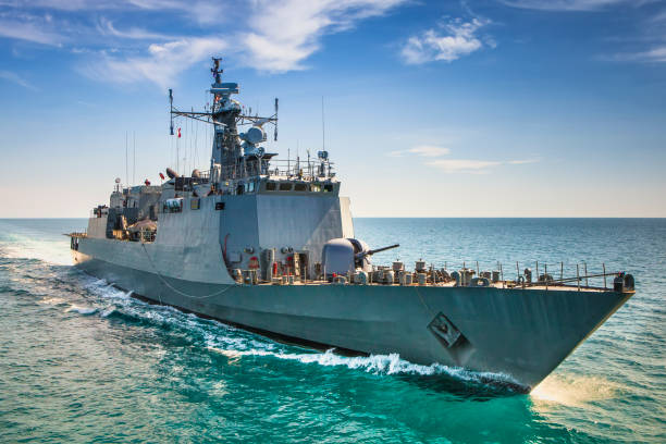 Grey modern warship sailing in the sea stock photo