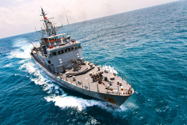 grey modern warship sailing in the sea - navy stock photos and pictures