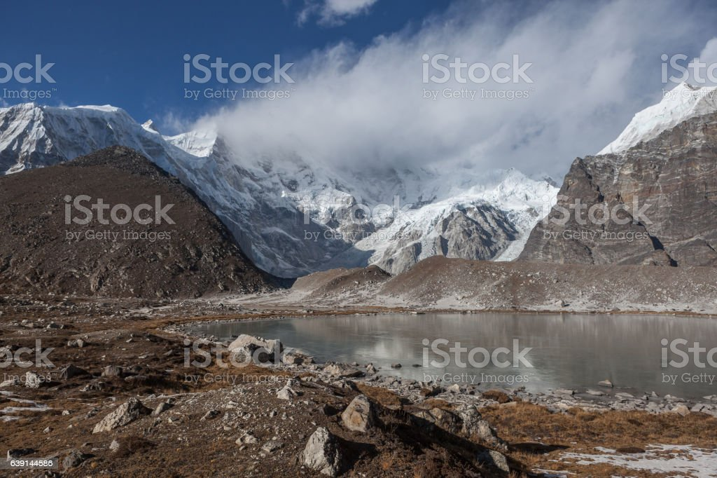 Grey moraine lake and snowy mountain peak covered stock photo