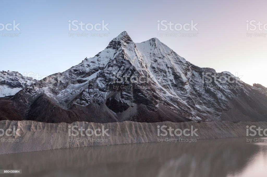Grey moraine lake and snowy mountain peak in the morning lights in Himalayas, Nepal. Mirror water of a big moraine lake. Imja Tsho moraine lake at the foot of the Imja Glacier. stock photo