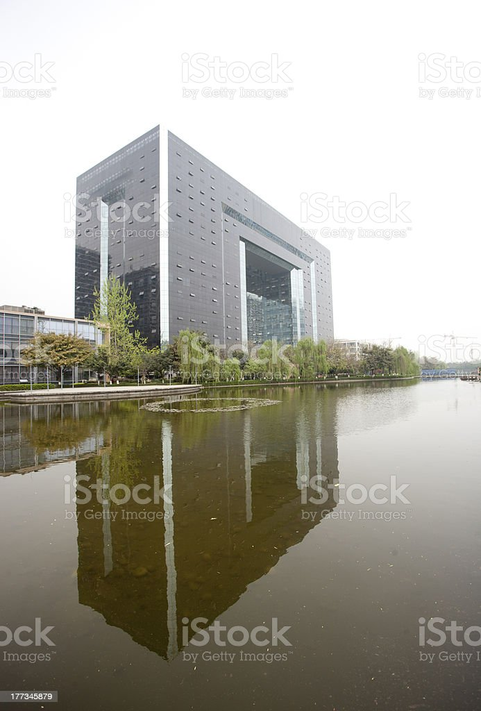 grey office building reflected in the lake royalty-free stock photo