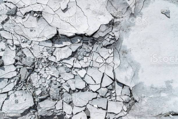 Photo of Grey pattern or textured background with cracked concrete.