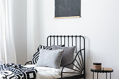 Grey pillows and patterned sheets on bed in white bedroom interior with black poster. Real photo