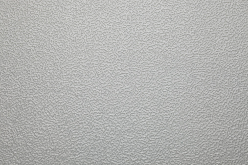 An abstract picture of a grey pattern of ridges on a plastic surface.