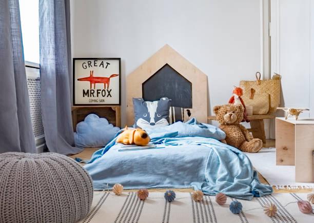 graue hocker auf teppich in des kindes schlafzimmer innenraum mit plüschtier neben blauen bett. echtes foto - fuchs kissen stock-fotos und bilder