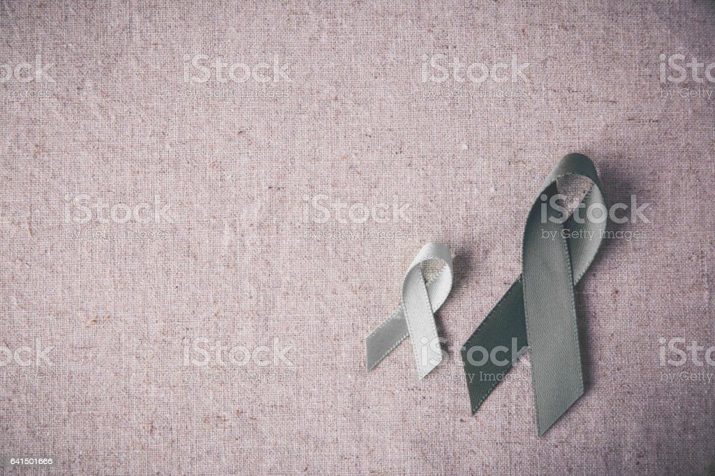 grey ribbons on linen toning background, Brain cancer awareness, Brain Tumors,Asthma awareness, Allergies and Diabetes awareness stock photo