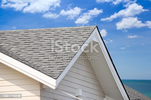 istock grey roof shingle with blue sky background, house roof near sea in morning time. 1091716296