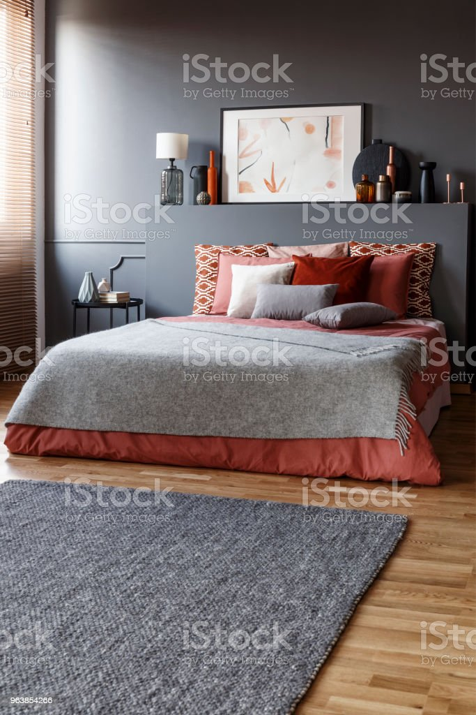 Grey rug in front of a king size bed with pillows and a painting above in a simple bedroom interior - Royalty-free Above Stock Photo