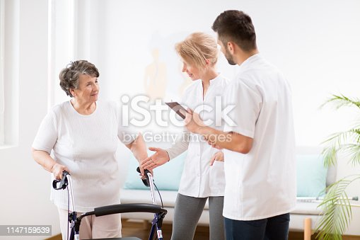 950649706istockphoto Grey senior lady with walker during physiotherapy with professional female doctor and male nurse 1147159539