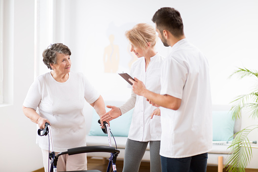 950649706 istock photo Grey senior lady with walker during physiotherapy with professional female doctor and male nurse 1147159539