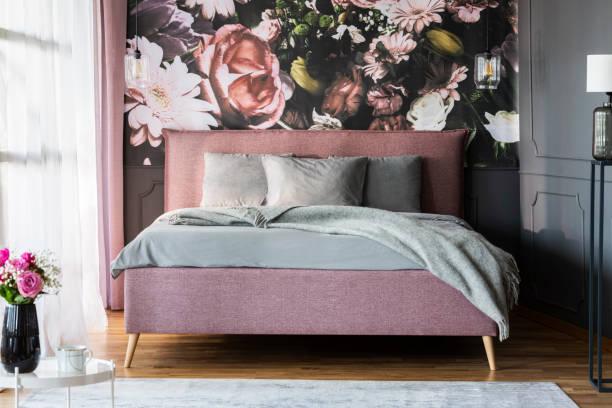 graue blätter auf rosa bett im weiblichen schlafzimmer innenraum mit flowerss druck auf die wand. echtes foto - blumendrucktapete stock-fotos und bilder