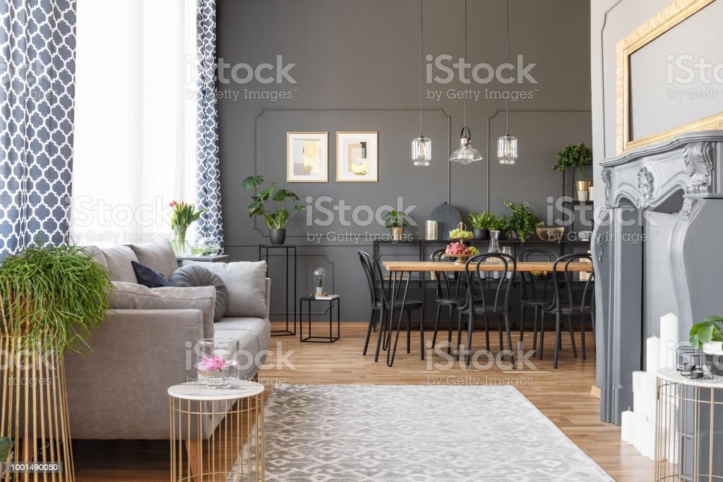 Grey sofa and posters on the wall in modern open space interior with chairs at dining table. Real photo stock photo