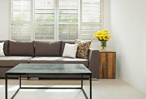graues sofa im kleinen rahmen - hofladen stock-fotos und bilder