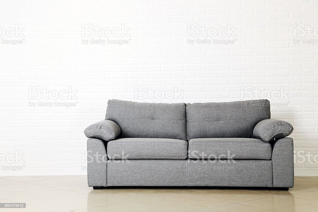Grey sofa on a white brick wall background stock photo