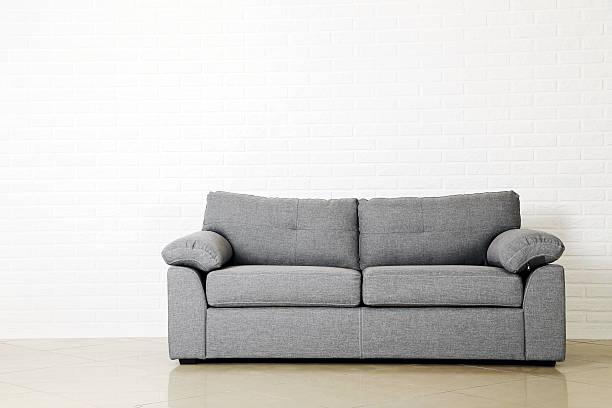 Grey sofa on a white brick wall background stock photo