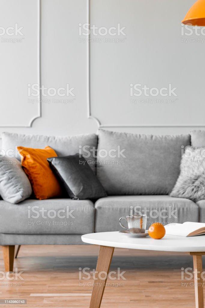 Graues Sofa Mit Kissen Und Ein Couchtisch Mit Orange Im ...