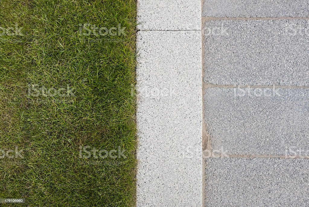 Grey stone paving & kerb adjacent to green grass lawn stock photo