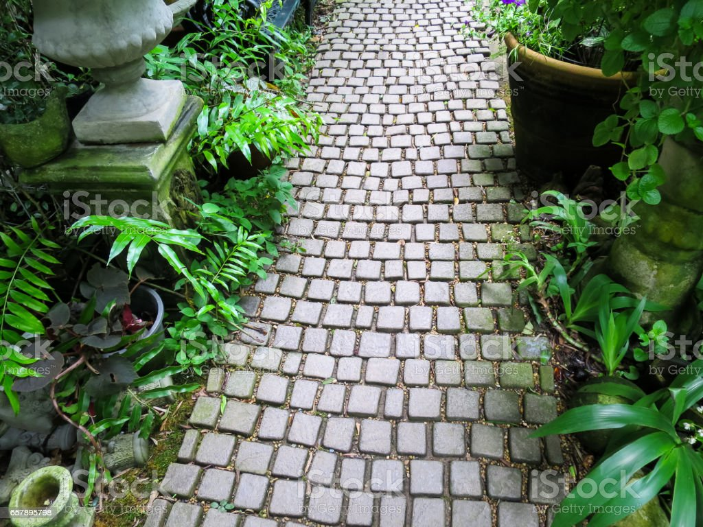 grey stone walkway through english style garden along with green