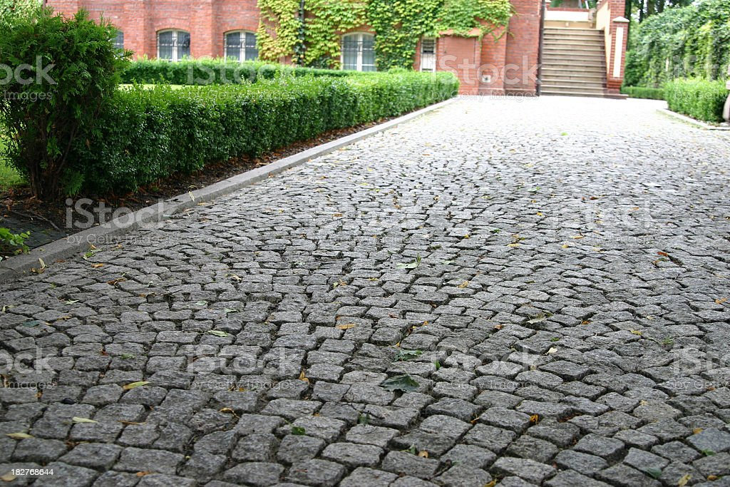 Grey stoned paved driveway lined with green shrubs royalty-free stock photo