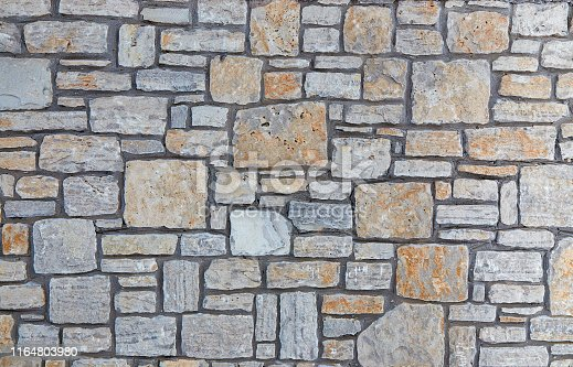 Grey stone wall with interesting texture of stones. Vintage background of grey wall.