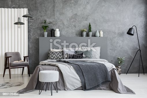 Grey stool in front of bed with blankets and cushions in dark hotel bedroom interior. Real photo