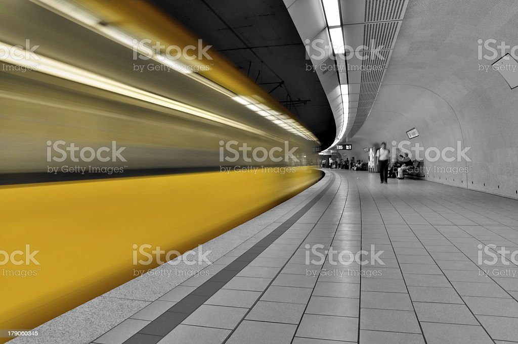 Grey subway station with bright yellow time lapse of train royalty-free stock photo