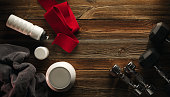 Grey towel Protein shake bottle Dumbbell plate White jar with whey protein Red hand wrap Sneakers on wooden floor