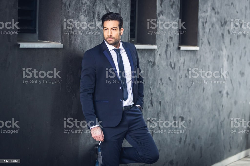 Grey wall and black suit stock photo