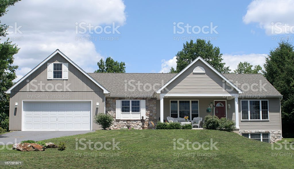 Grey wood and stone ranch home with blue sky and trees  stock photo