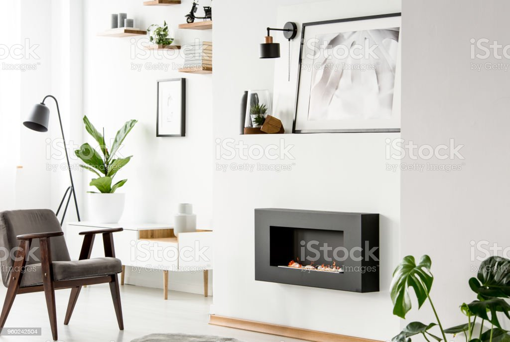 Grey wooden armchair in front of fireplace in white flat interior with poster and plant. Real photo stock photo