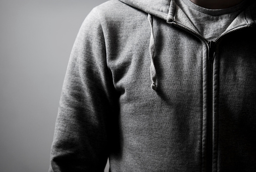 Close up of a grey zip top hoodie in high contrast.