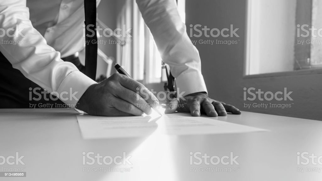 Greycale image of a man signing contract or document stock photo