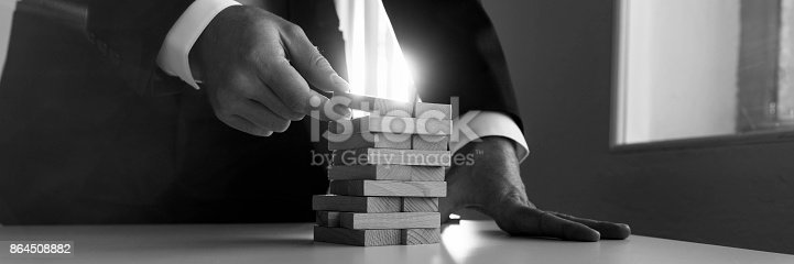 istock Greycale panorama view of businessman placing wooden domino in a tower 864508882