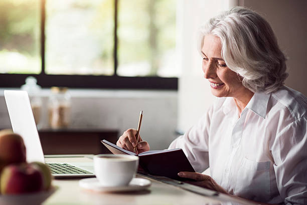Grey-haired lady taking notes with pencil and using laptop stock photo