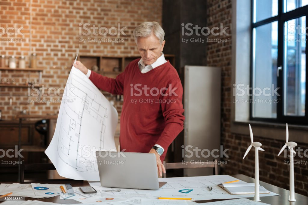 Grey-haired man holding blueprint and typing on laptop stock photo
