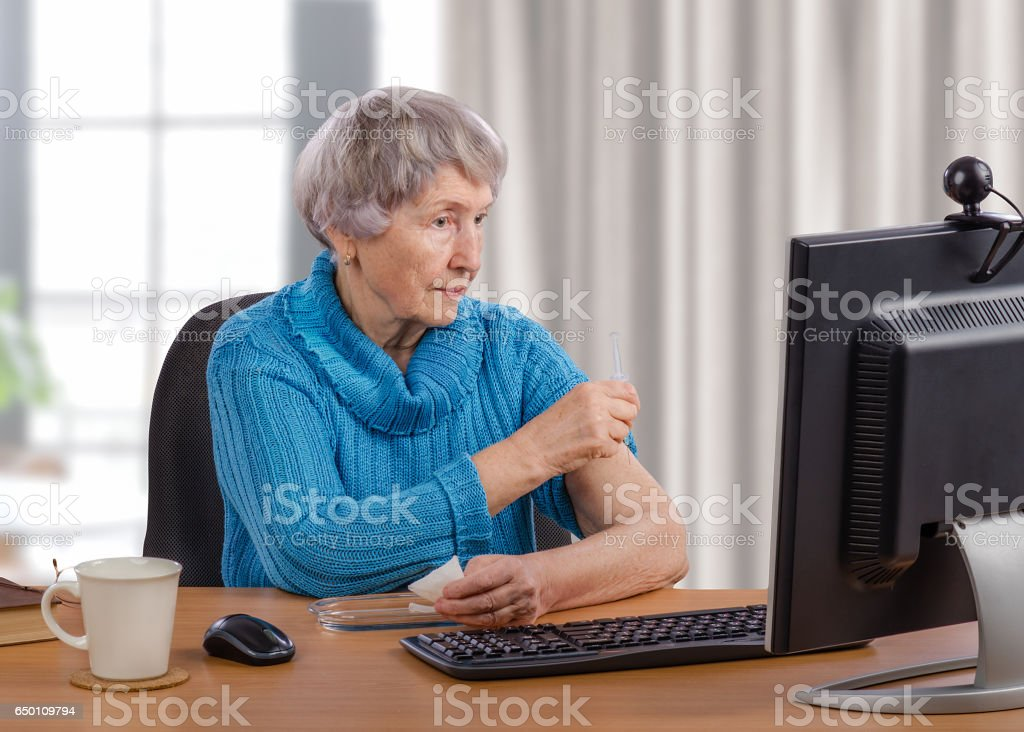 Grey-haired old woman gives an intramuscular injection in front of monitor stock photo
