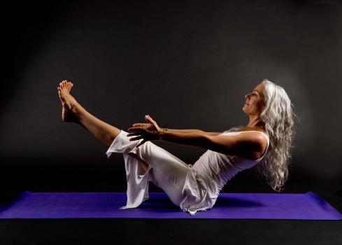 greyhaired senior woman holding a yoga pose stock photo