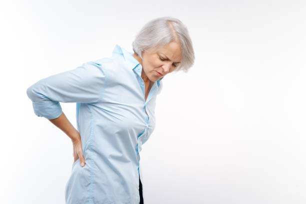 Grey-haired woman suffering from pain in lower back stock photo