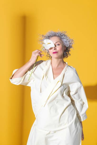 çiçekle poz veren kıvırcık saçlı gri saçlı kadın - beyaz elbise stok fotoğraflar ve resimler