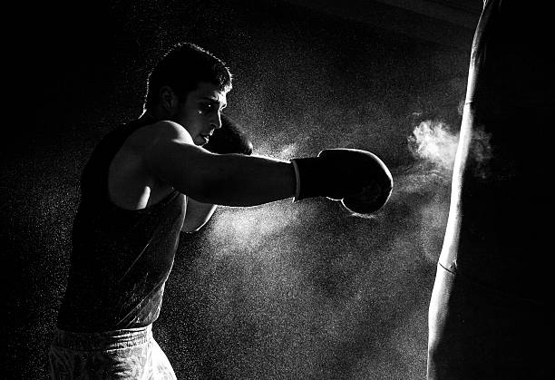 Greyscale image of a boxer having a go at the punching bag stock photo